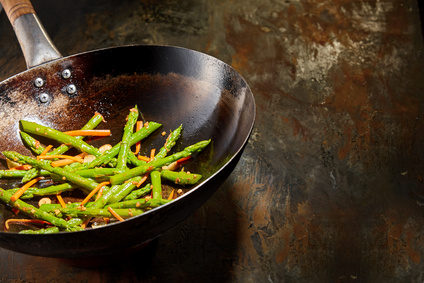 Healthy fresh green asparagus shoots cooked with diced carrots and savory seasoning served in an old rustic frying pan on a rusty metal surface with copy space