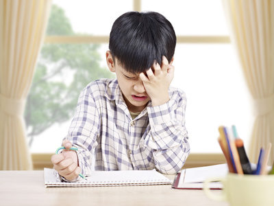10 year-old asian elementary schoolboy appears to be frustrated while doing homework at home.