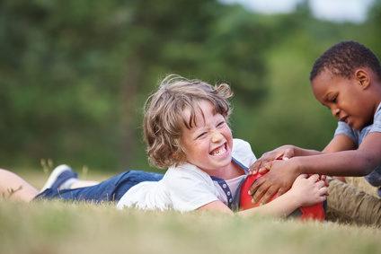 Zwei Jungen sind Freunde und liegen mit einem Fußball im Gras