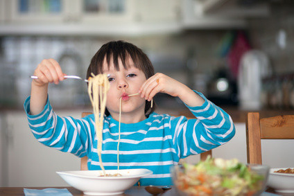 Cute little boy, eating spaghetti at home for lunchtime, tasty food