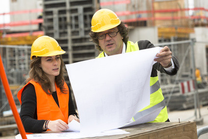 Two engineers on building site checking plans